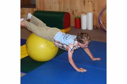 Child balancing on exercise ball to strengthen neck and shoulders.