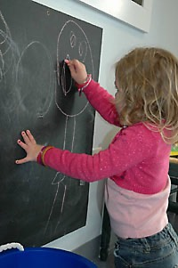Child practicing hand/eye coordination at a chalkboard.
