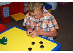 Child sorting small objects to improve fine motor coordination.