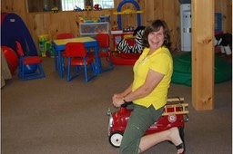 Humorous image of OT in Motion owner Jan Halley playing with toys in physical therapy room.
