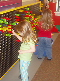 Children engaging in hand/eye coordination exercise at pegboard.