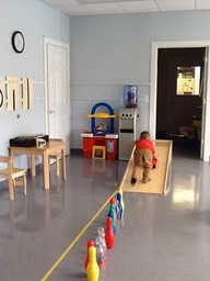 Child in an indoor obstacle course engaging in motor planning exercise.